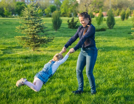 Beautiful mother lifts high her cheerful girl and begins turning her around. They are smiling. Happy family time playing with daughter in park. Stock Photo