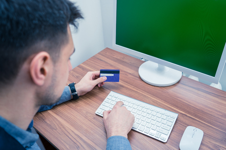 pin code: Office worker holding credit card and making online purchase