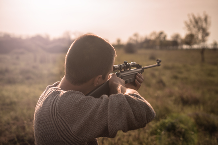 The man takes aim at the target with a sniper rifle. Selective Focus Reklamní fotografie