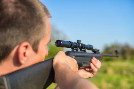 The man takes aim at the target with a sniper rifle. Selective Focus Stock Photo