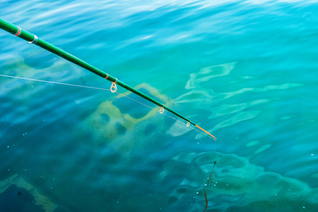Amateur fishing rod in clear blue water Stock Photo