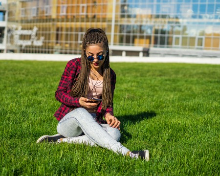 Young beautiful girl with zizi cornrows dreadlocks listening to music sitting on the lawn Stock Photo
