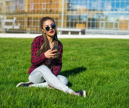 Young beautiful girl with zizi cornrows dreadlocks listening to music sitting on the lawn Archivio Fotografico