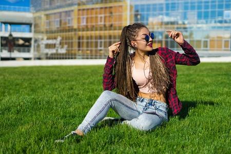 girl with zizi cornrows dreads listening to music
