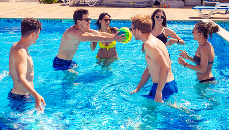 Group of cheerful couples friends playing water volleyball Stockfoto