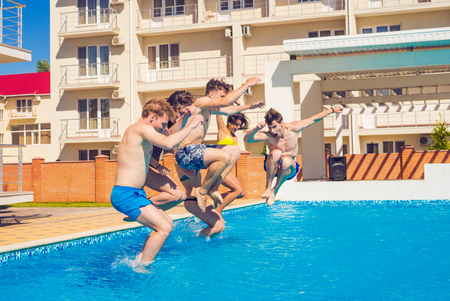 freezed: Party at smimming pool. Group of cheerful friends jumping into water. Stock Photo