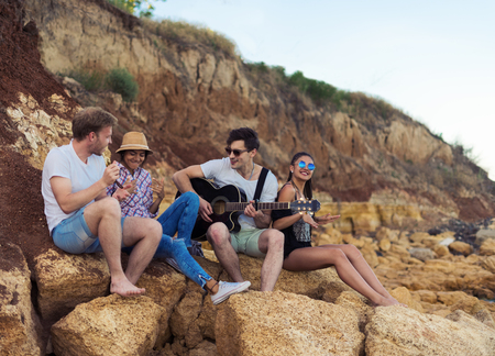 friends sitting on stones on beach. man is playing guitar. Stock Photo
