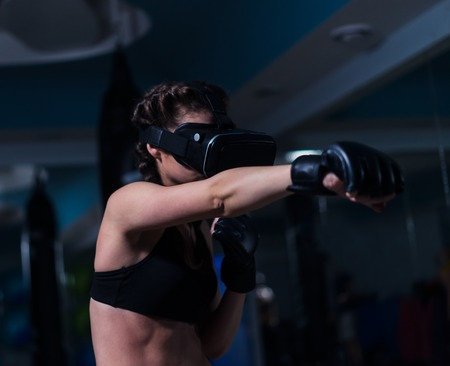 Young fighter boxer fit girl in VR glasses wearing boxing gloves