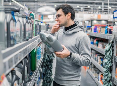 mannelijke klant koopt motorolie in de autosupermarkt