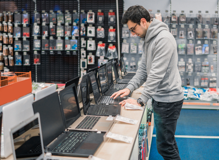 modern male customer choosing laptop in the computer shop