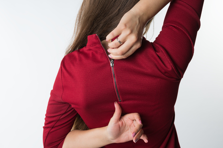 Woman pulling the zip up or down on her stylish red dress