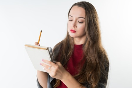 young caucasian pretty girl with sketchbook and pencil on white background