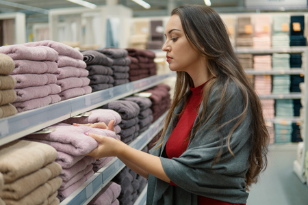 Female Customer inspecting and buying towels in supermarket