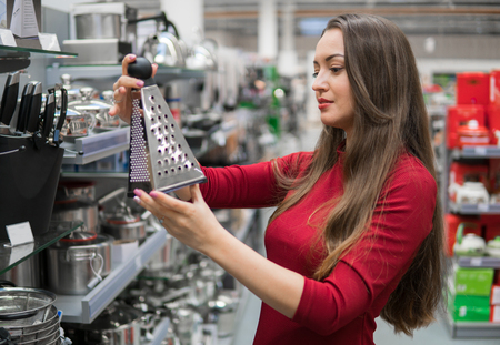Smart housewife woman buys kitchen grater in supermarket.