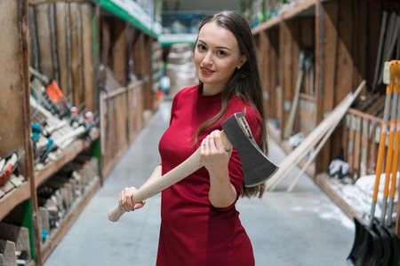Beautiful young woman holding an wooden handled axe Imagens