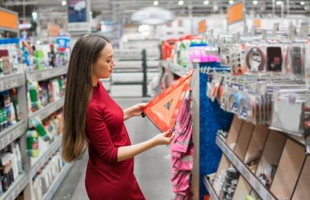 El conductor de sexo femenino joven compra el triángulo amonestador en el departamento de automóviles del supermercado. Foto de archivo - 91746361