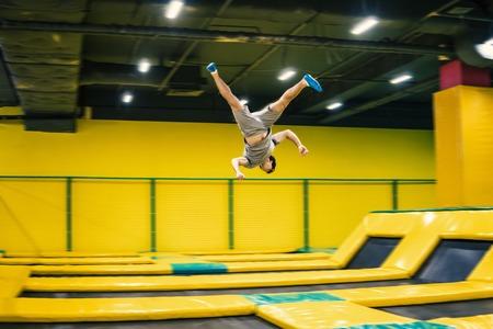 saltador de trampolín realiza ejercicios acrobáticos en el trampolín