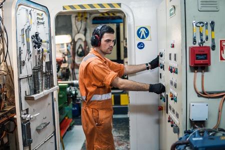 Oficial ingeniero marino controlando los motores del buque en la sala de control de motores ECR