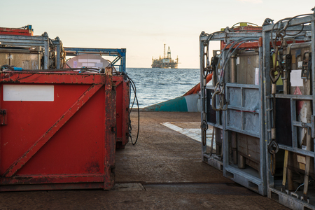 offshore supply boat delivers cargo to oil rig platform