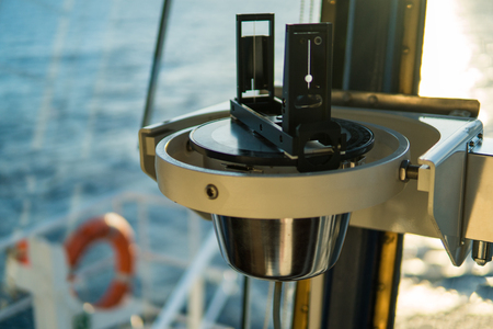Close up of nautical marine magnetic compass on yacht or boat