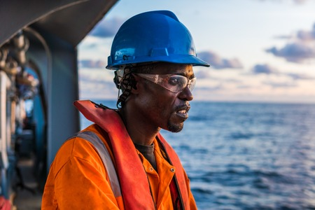 Seaman AB or Bosun on deck of vessel or ship , wearing PPE Stock Photo