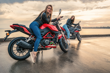 Two Biker girls in leather jackets on a black and red color sport motorcycles