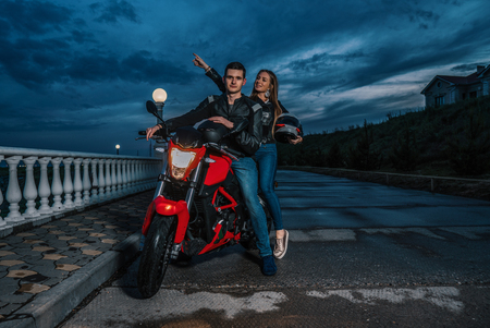 Biker couple man and woman on a black and red color sport motorcycle