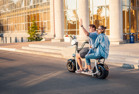 Lovely young happy couple driving electric bike
