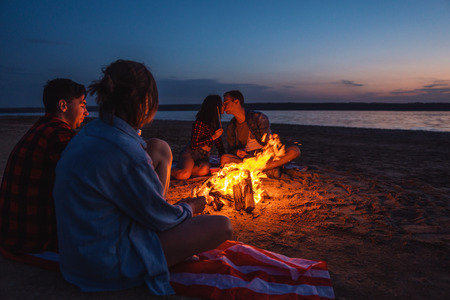 young friends have picnic with bonfire on the beach