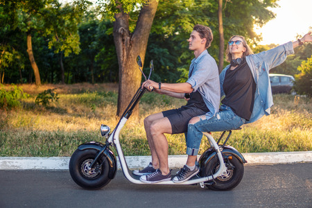 Lovely young couple driving electric bike during summer