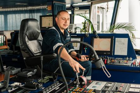 Marine navigational officer is maneuvering ship or vessel
