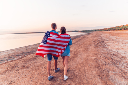 american couple covered in american flag walking on beach