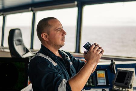 Navigational officer lookout on navigation watch looking through binoculars