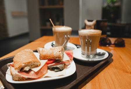 breakfest snack - coffee latte and bocadillo sandwich on table in one cafe Stock Photo