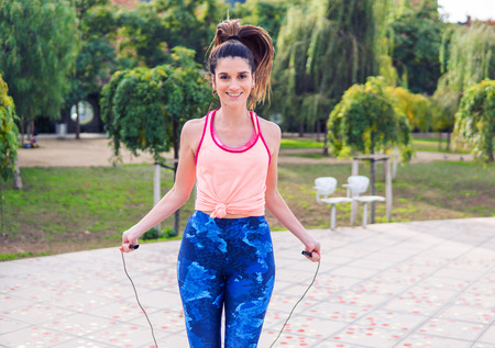 Fit beautiful woman with jumping rope in a park