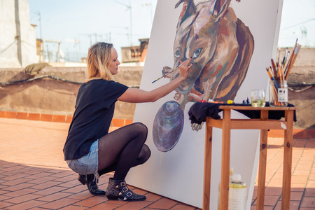 Young woman paint artist drawing at home roof