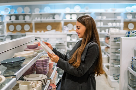 woman choosing utensil dishes in a store supermarket Stock Photo