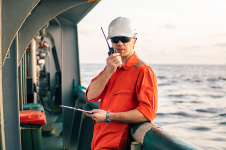 Deck Officer on deck of offshore vessel holds VHF walkie-talkie radio Stock Photo