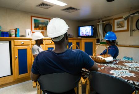 Seamen crew onboard a ship or vessel having fun watching TV