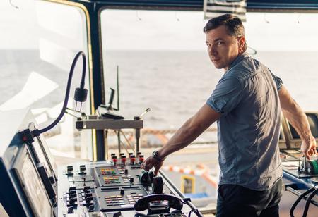 Marine navigational officer during navigational watch on Bridge Фото со стока