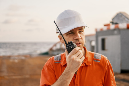 Deck Officer on deck of offshore vessel holds VHF walkie-talkie radio 版權商用圖片