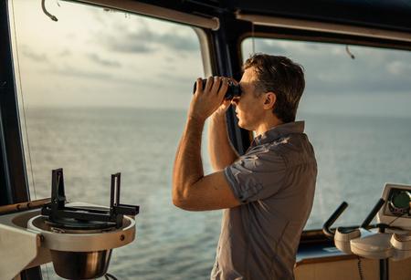 Navigational officer lookout on navigation watch with binoculars
