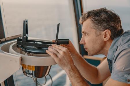 ufficiale di coperta che rileva l'errore della bussola magnetica a bordo della nave Archivio Fotografico