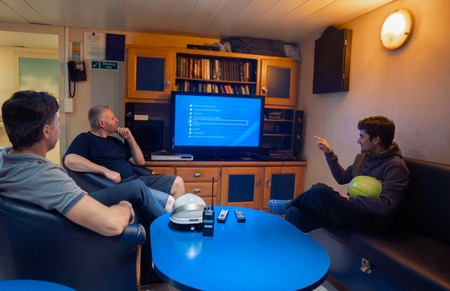 Happy team of ship officers watch TV onboard of vessel