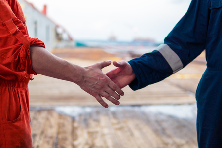 marine contractor businessman handshaking with worker on the ship.
