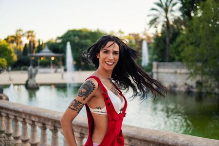 Ladyboy tattooed transgender model is dancing in the green park Reklamní fotografie