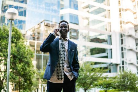 African American businessman holding mobile phone wearing blue suit