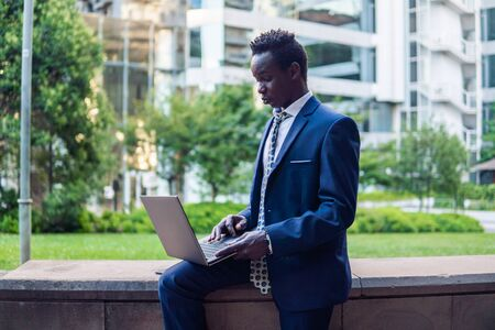 African American businessman holding laptop notebook wearing blue suit