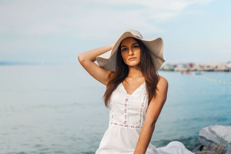 Pretty woman wearing white dress and pamela hat standing Reklamní fotografie
