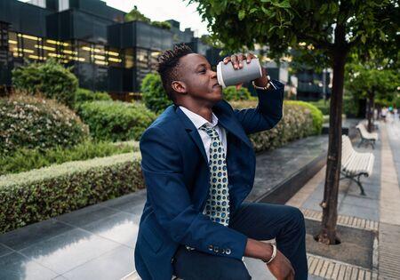African American businessman wearing blue suit drinks coffee near office